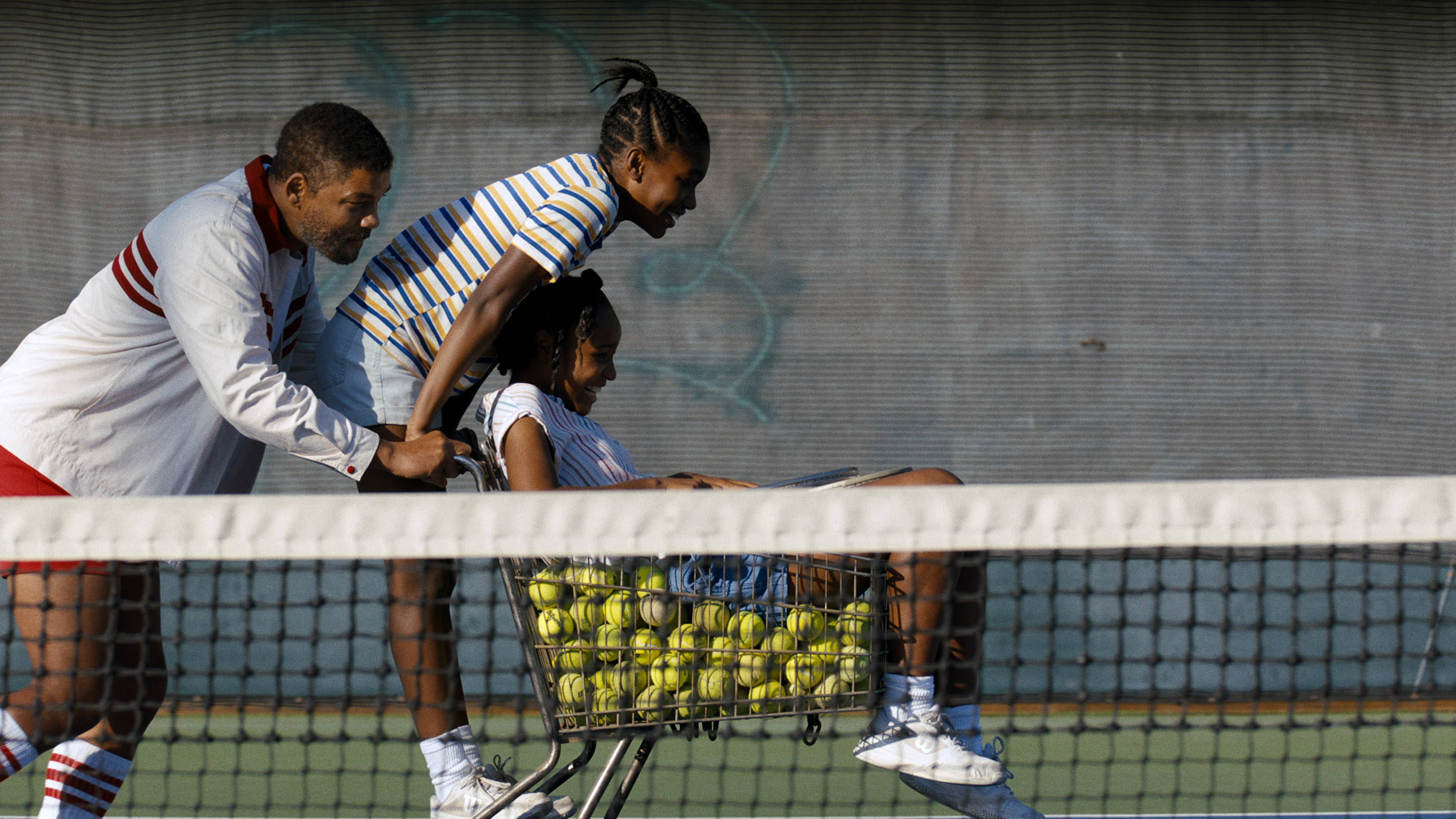 Richard pushing his daughters as they hang on to a shopping cart filled with tennis balls in a scene from the film