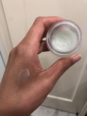 buzzfeed editor holding a pot of and swatching clear eye cream