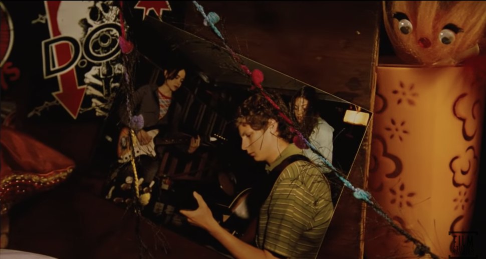 Michael Cera playing guitar in a photo on Juno's wall