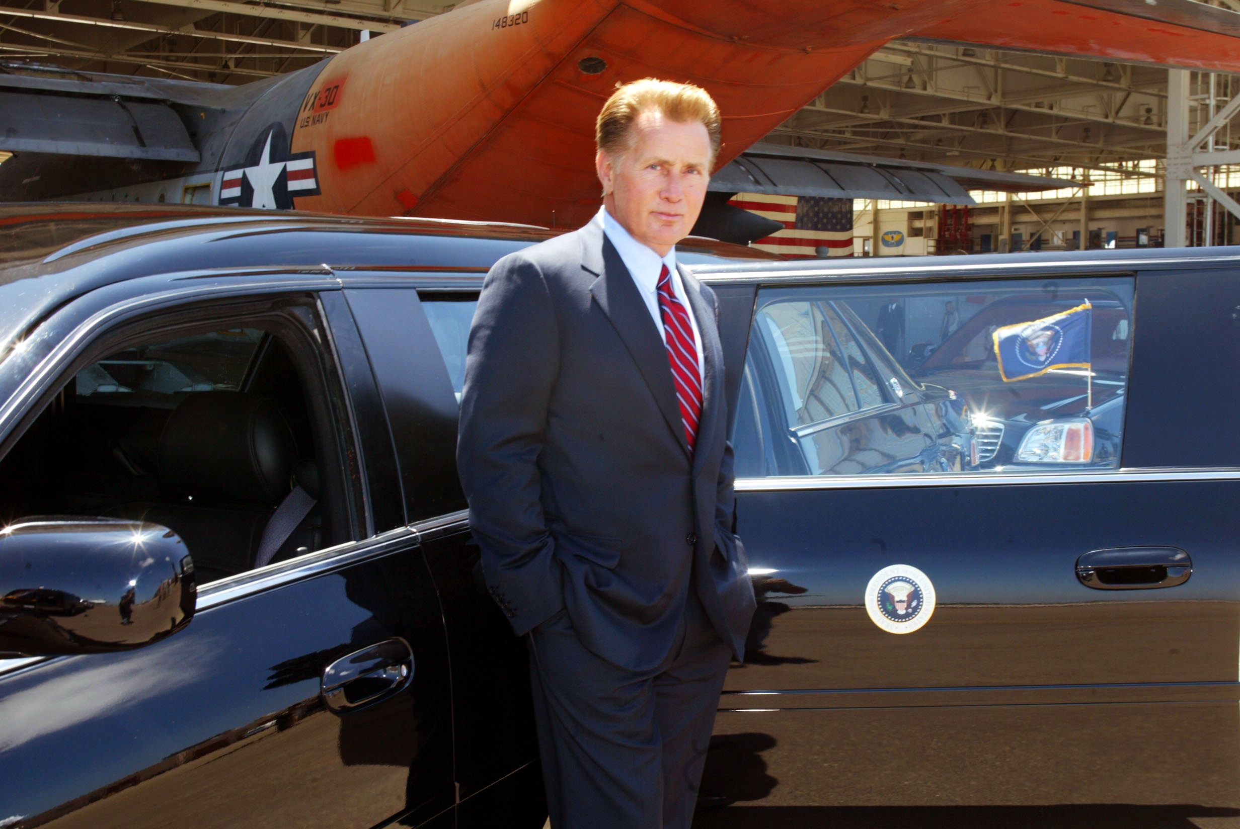 Martin Sheen as President Josiah Bartlet standing at his limo with the presidential seal