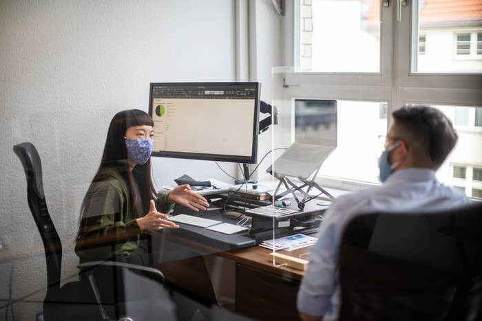 Office workers wearing masks and using glass partitions between their desks