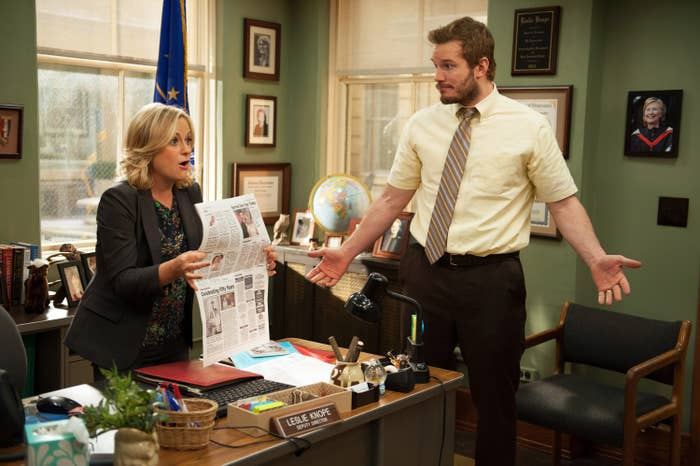 """Andy standing next to Leslie's desk in """"Parks and Rec"""""""