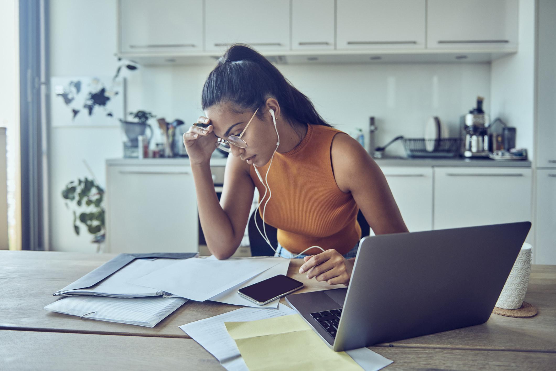 Woman looking at financial paperwork at home