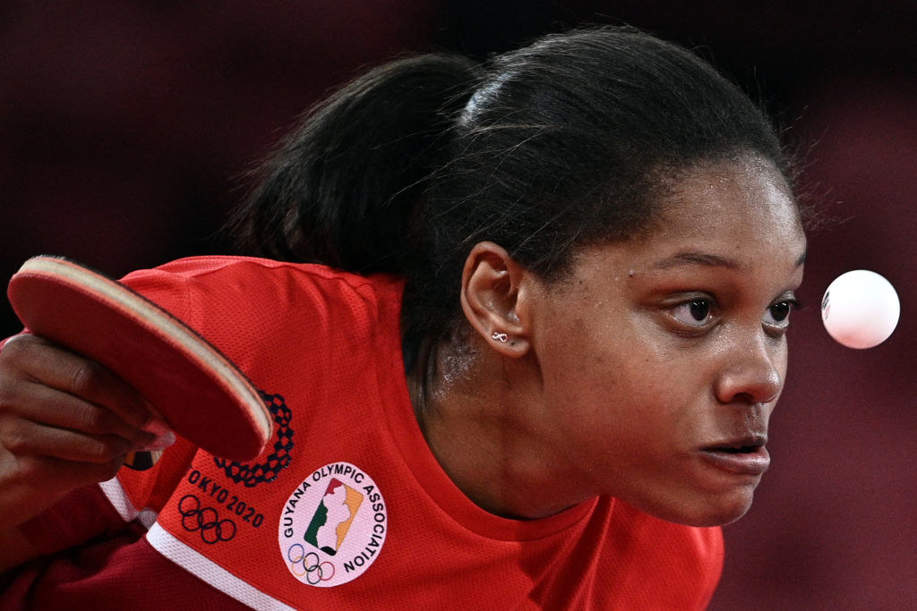 A Guyanese athlete staring intently at the ball as she takes a shot