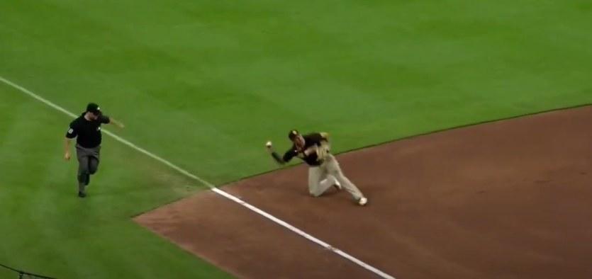 Manny Machado throws a baseball while on one knee
