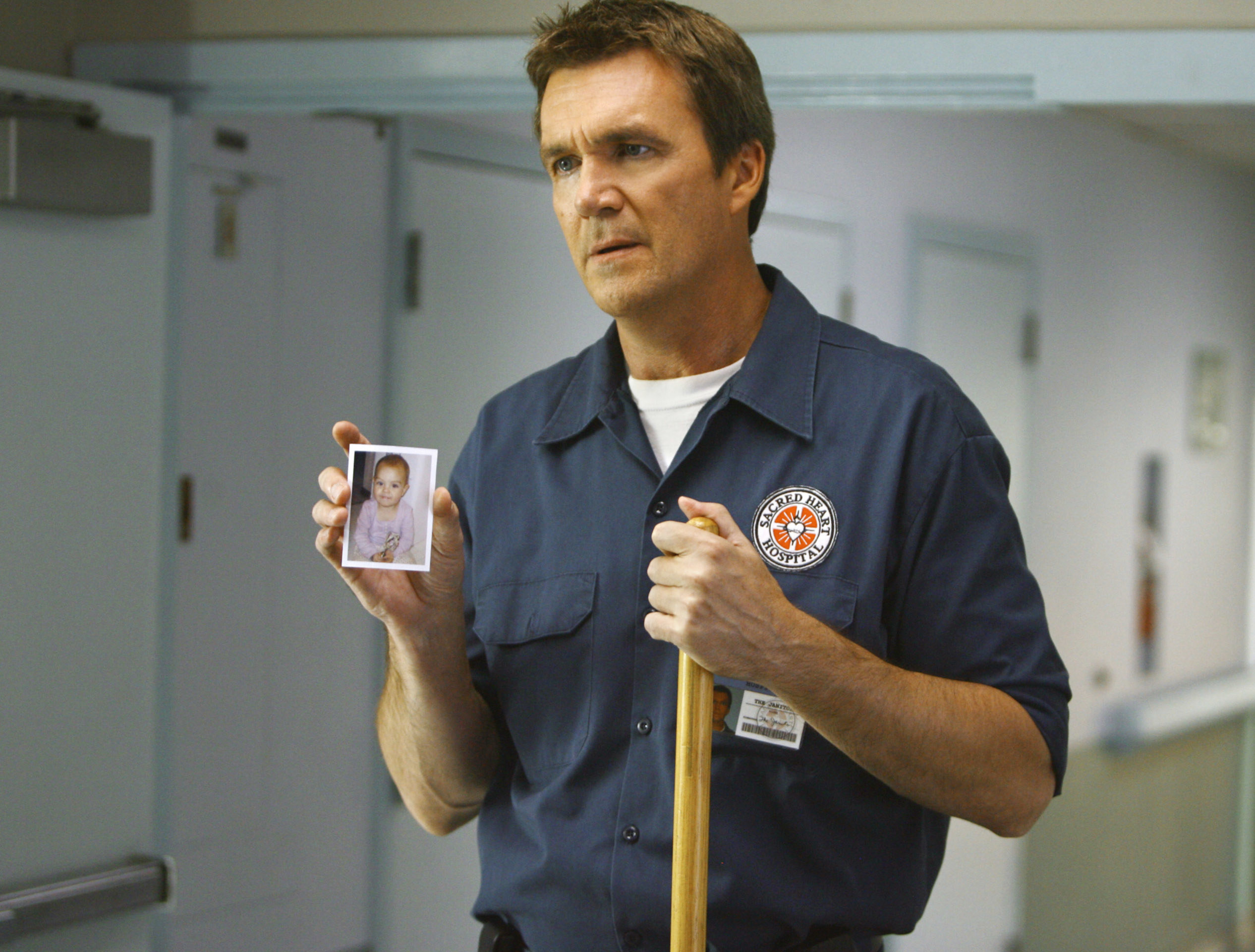 """The Janitor holding a broom and a photo of a baby on """"Scrubs"""""""