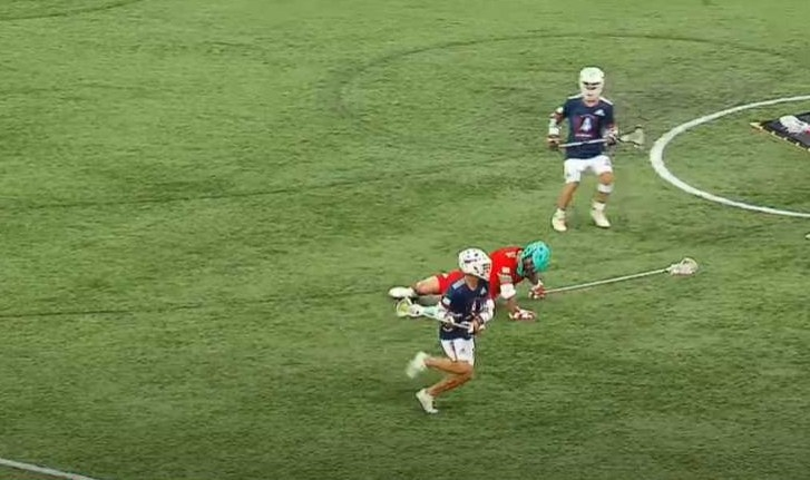 Lacrosse player on the ground while the ball-handler runs past him