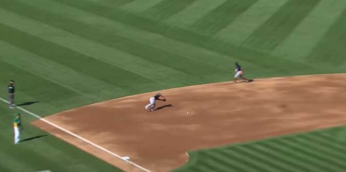 Baseball player dives for incoming baseball
