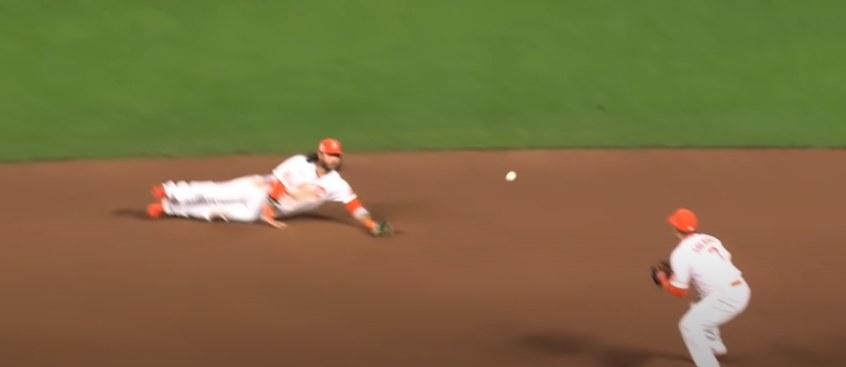 Downed baseball player flips ball to second baseman