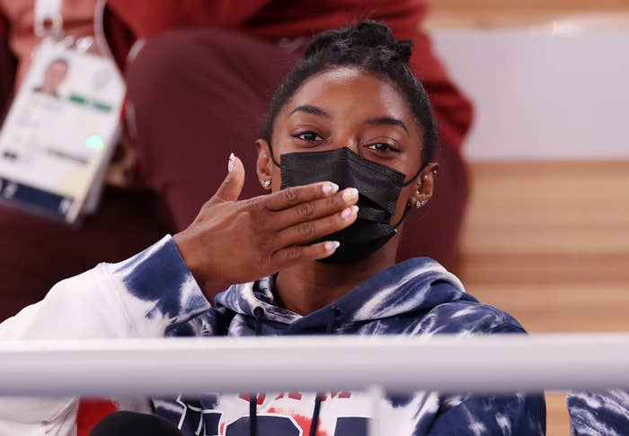 Simone Biles blowing a kiss while watching the Olympics