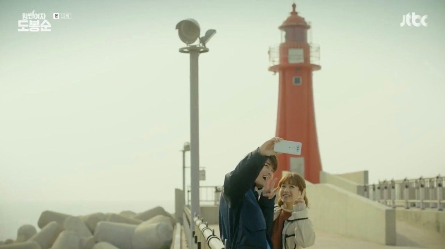 Couple taking picture in front of lighthouse