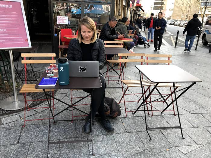 Woman on her computer in front of a café