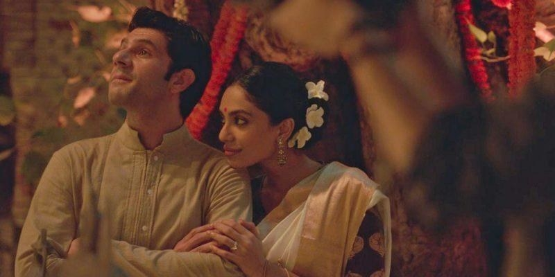 Tara leans on karan, who has his arms crossed, in a still from made in heaven