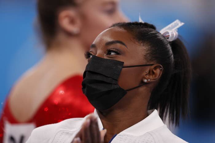 Simone Biles is shown wearing a face mask