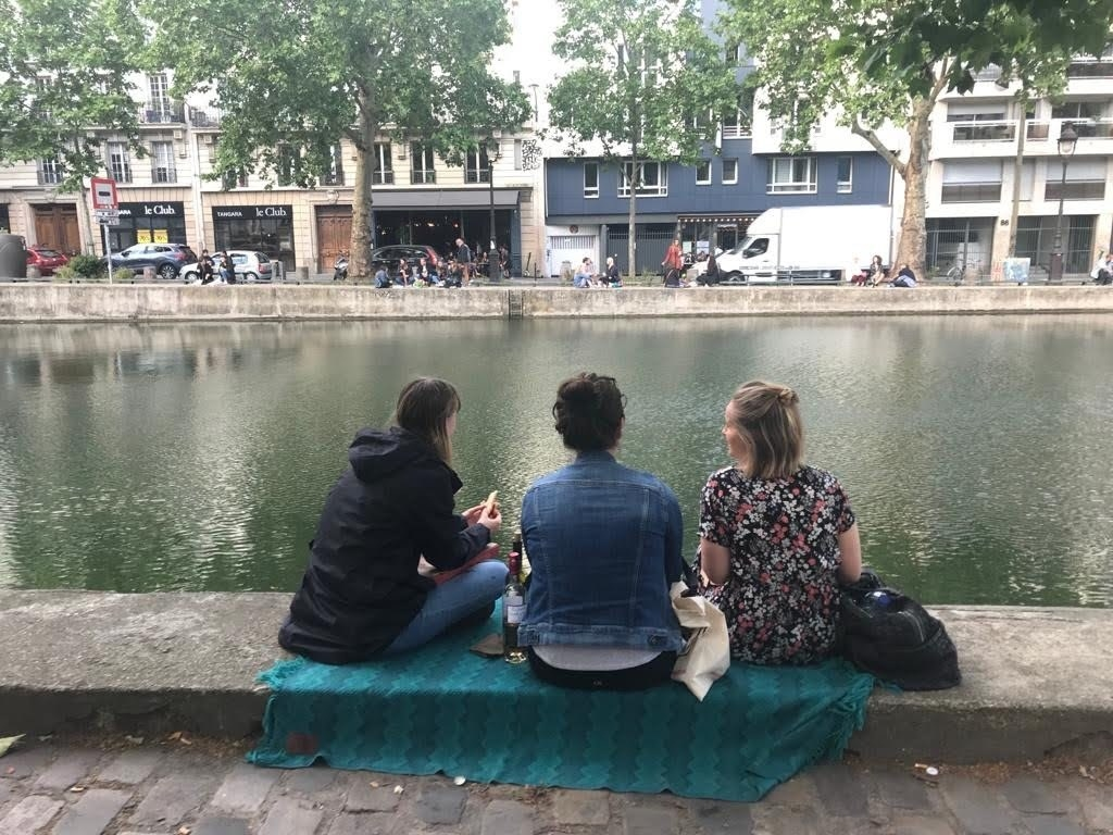 Three women sit by the water