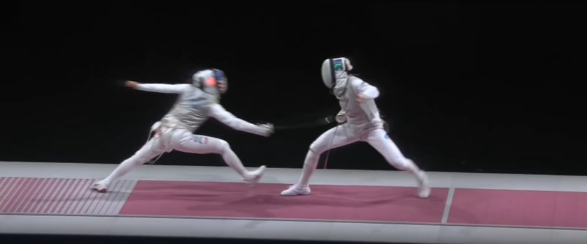 Fencer lunges forward with sword to hit her opponent