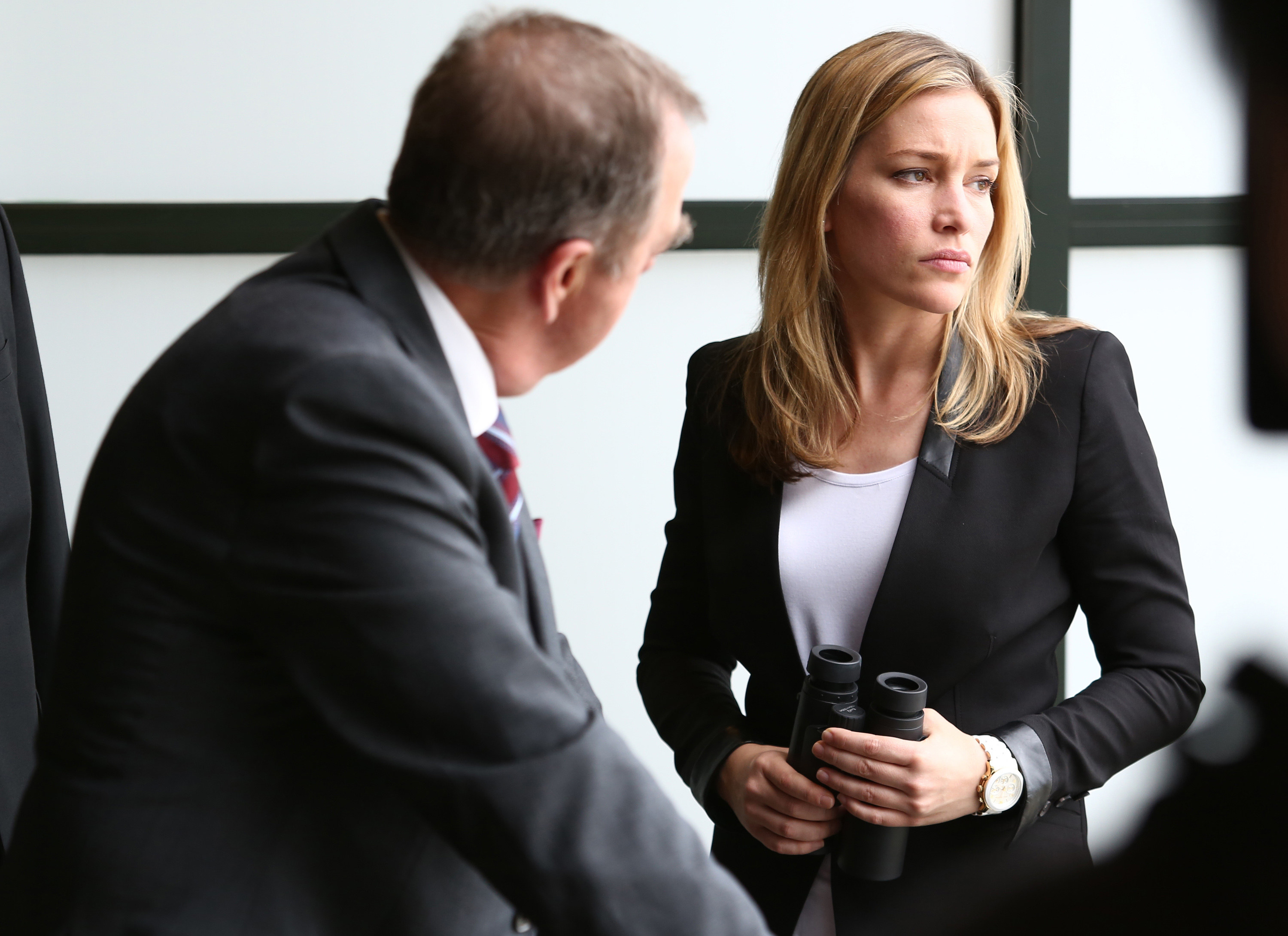 Gregory Itzin talks to Piper Perabo while she holds binoculars