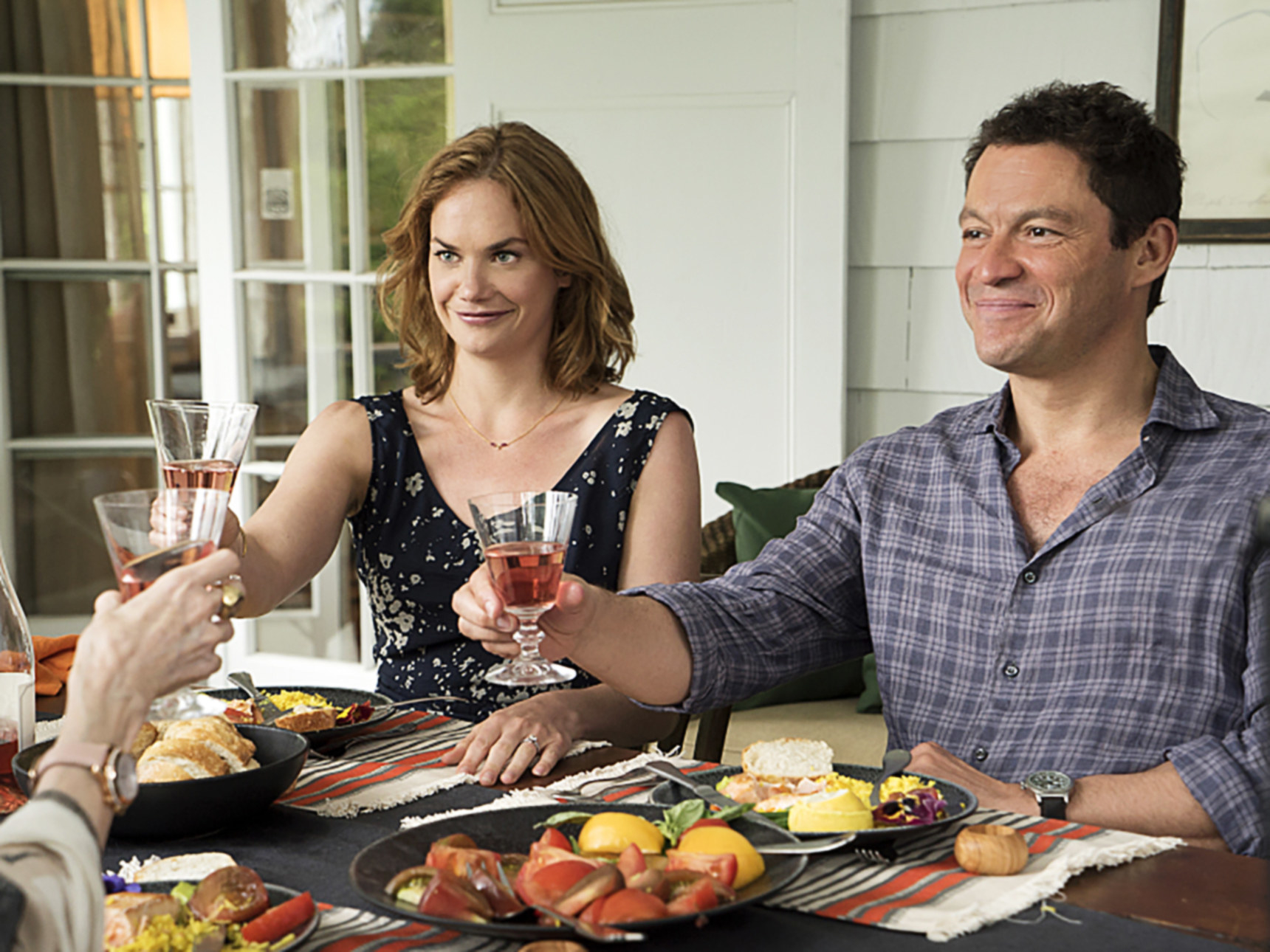 Ruth Wilson and Dominic West raise glasses at a table