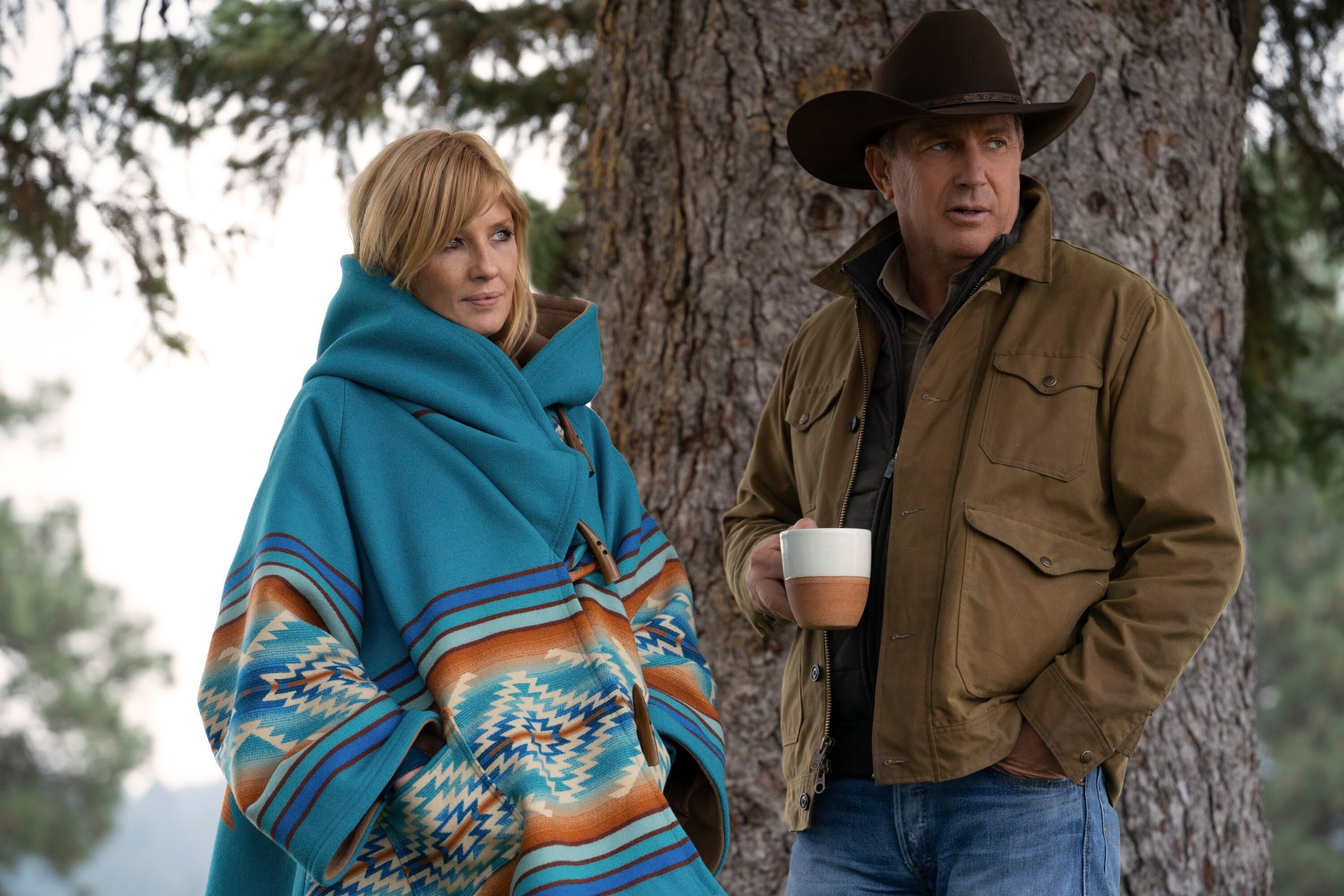 Kelly Reilly and Kevin Costner stand bundled near a tree