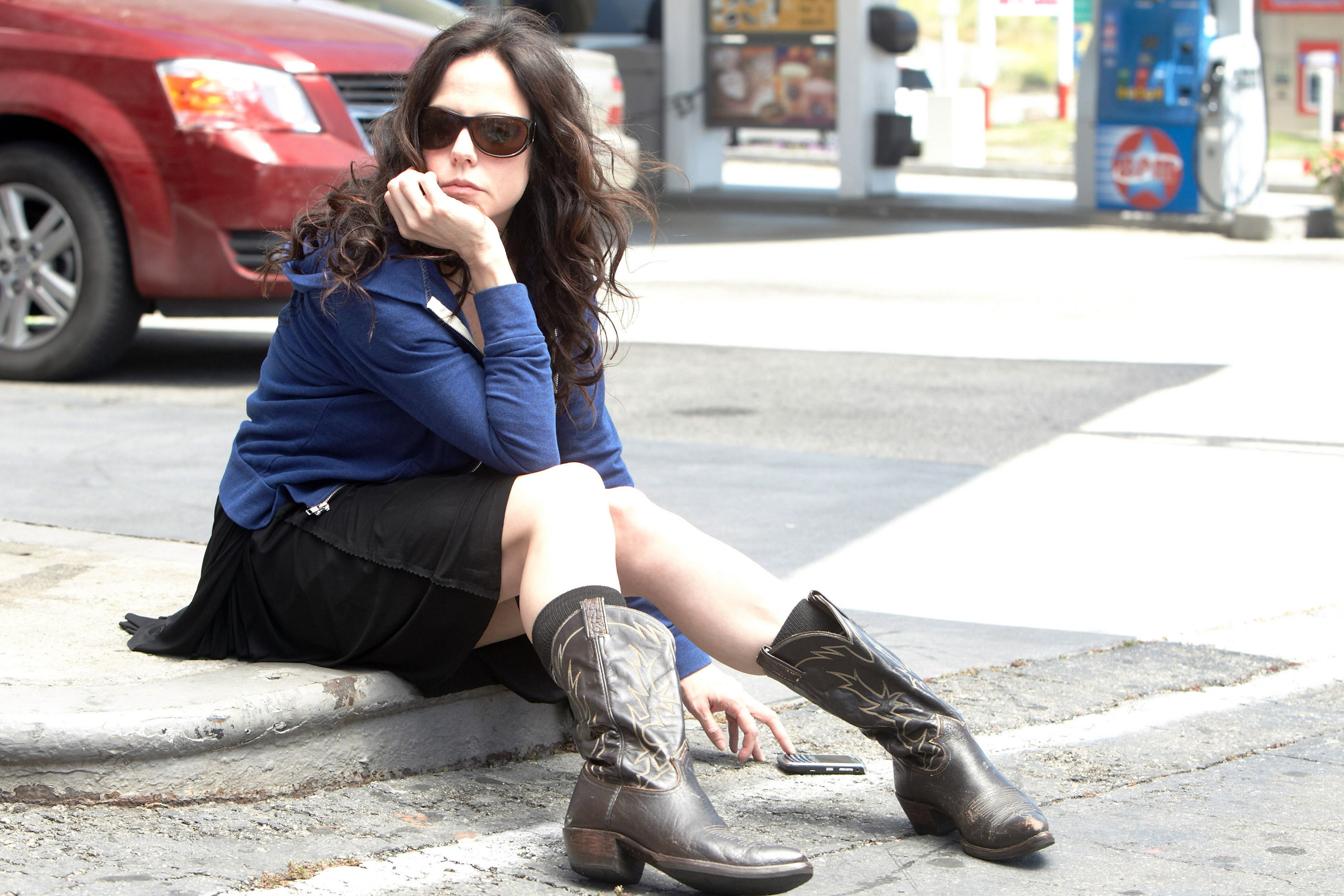 Mary-Louise Parker sits on the curb near a gas station
