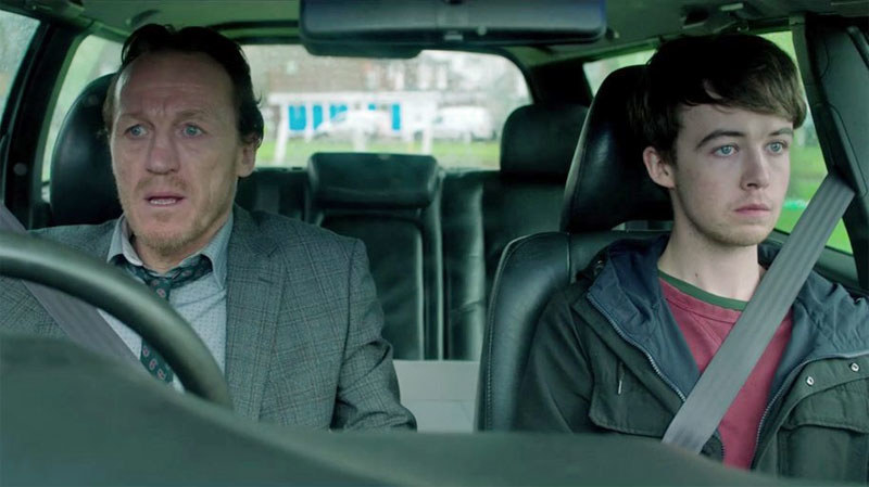 an older man and younger boy sit in the front seat of a car, eyes both wide and mouth shut as if scared