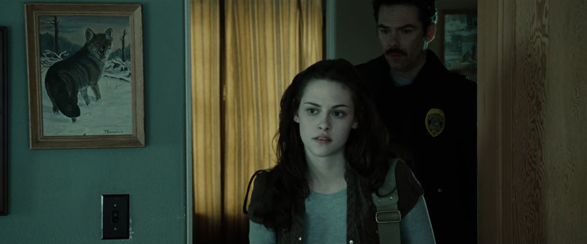 Bella walks into the room, which has a framed picture of a wolf