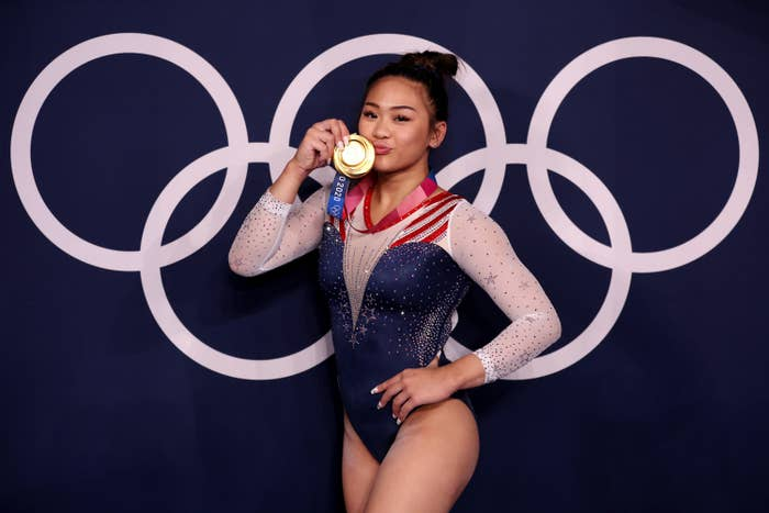 Suni Lee holding up her Olympic medal