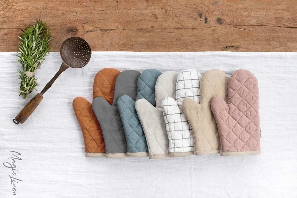 seven linen oven mitts of different colors
