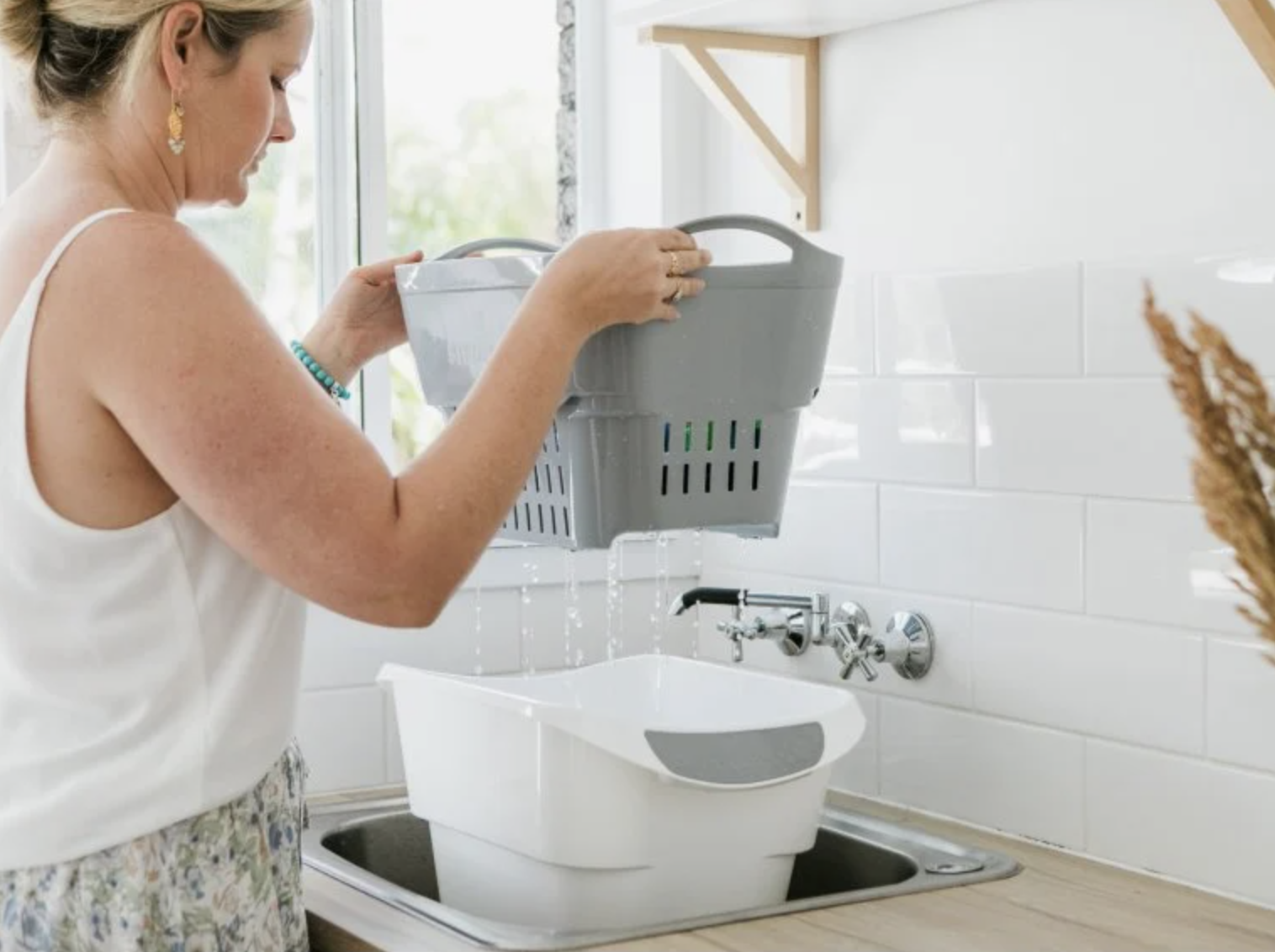a model lifts the hand washing strainer out of the bucket