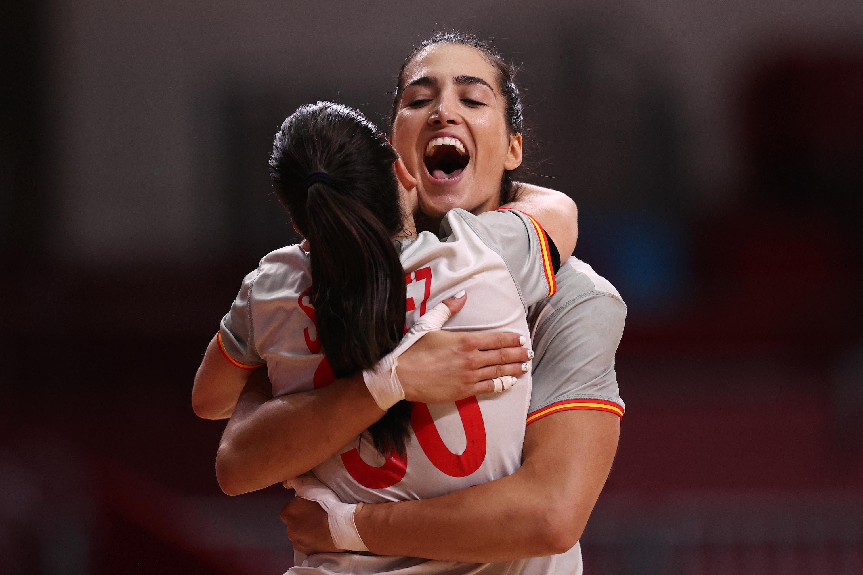 Two women athletes grin and hug after winning a handball match