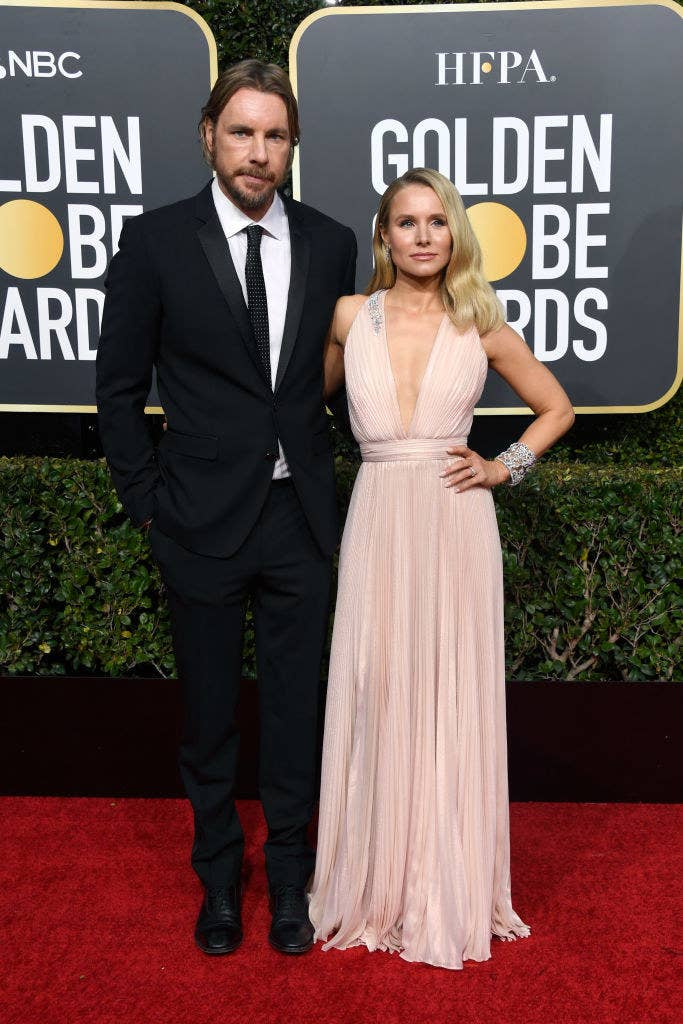 Dax and Kristen posing on the Golden Globes red carpet in a suit and low-cut gown, respectively