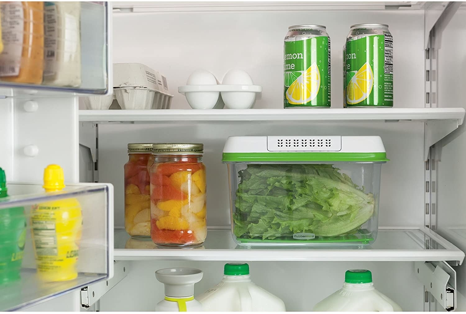 The produce saving box inside a fridge; it is filled with fresh lettuce