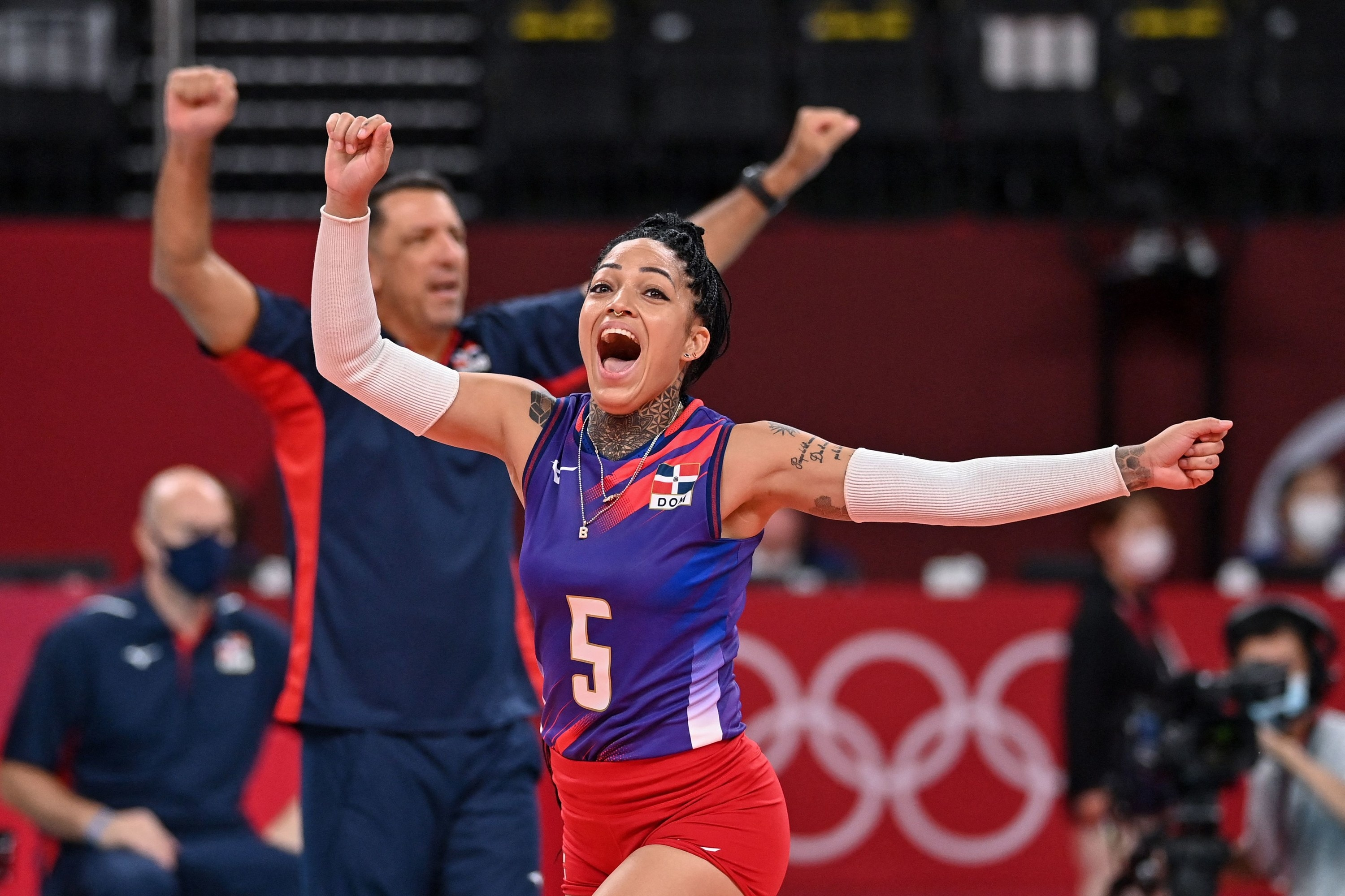 An Olympic volleyball player cheers with her arms outstretched