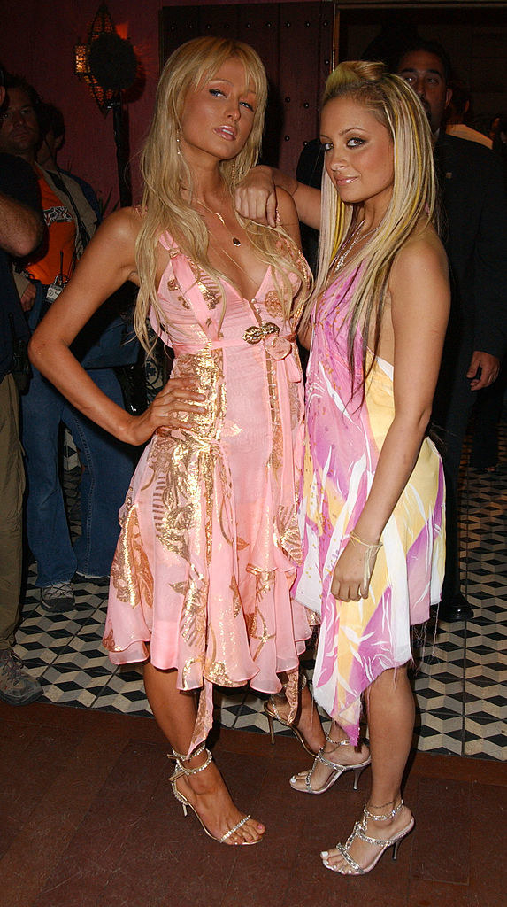 Paris Hilton and Nicole Richie embracing and both wearing pink-and-gold dresses with strappy high-heeled sandals