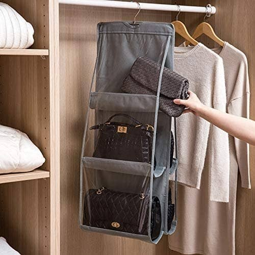 Someone putting a clutch purse into one of the transparent pockets on the hanger