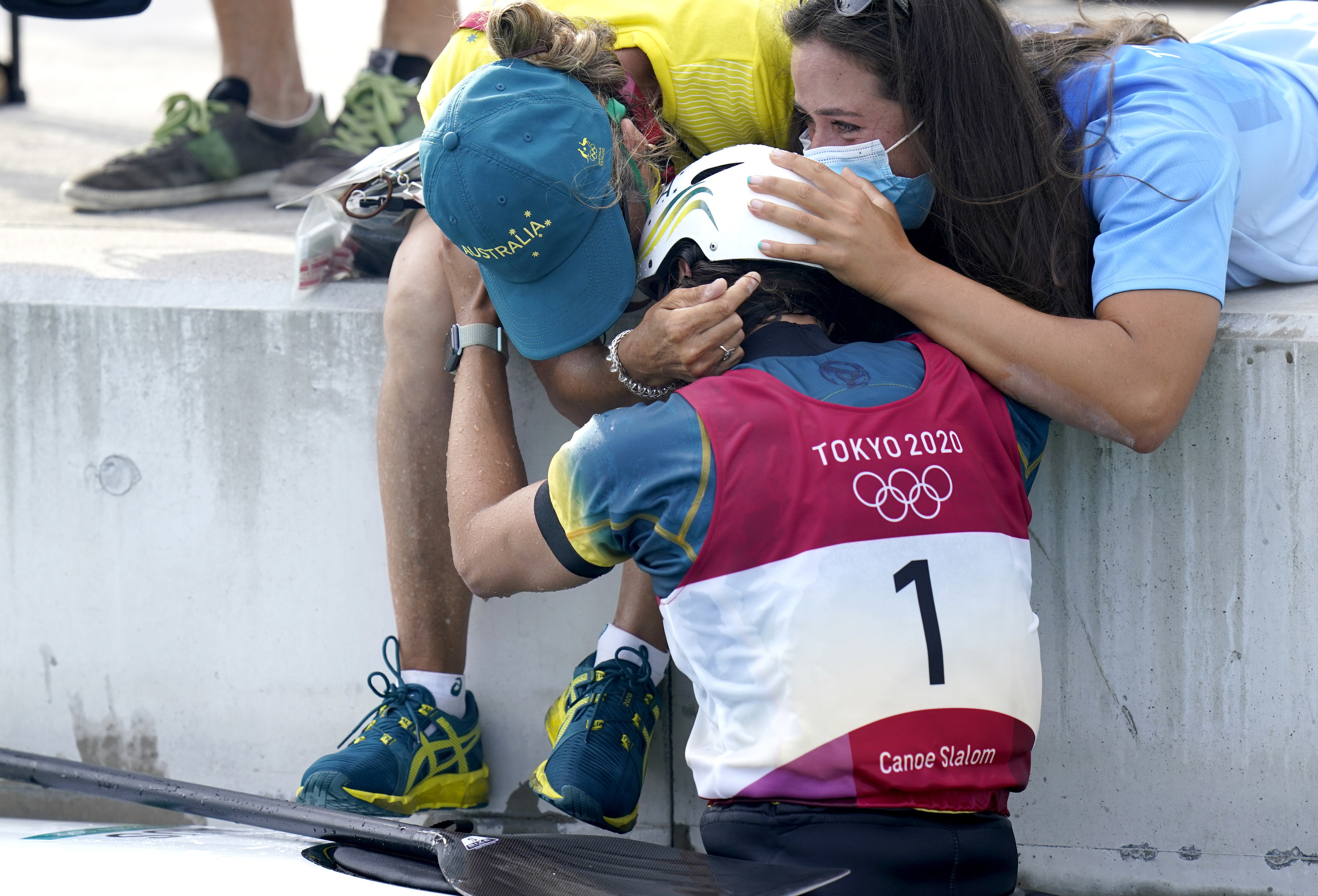 An athlete reaches out to hug her team after competing in the canoe slalom at the Olympics