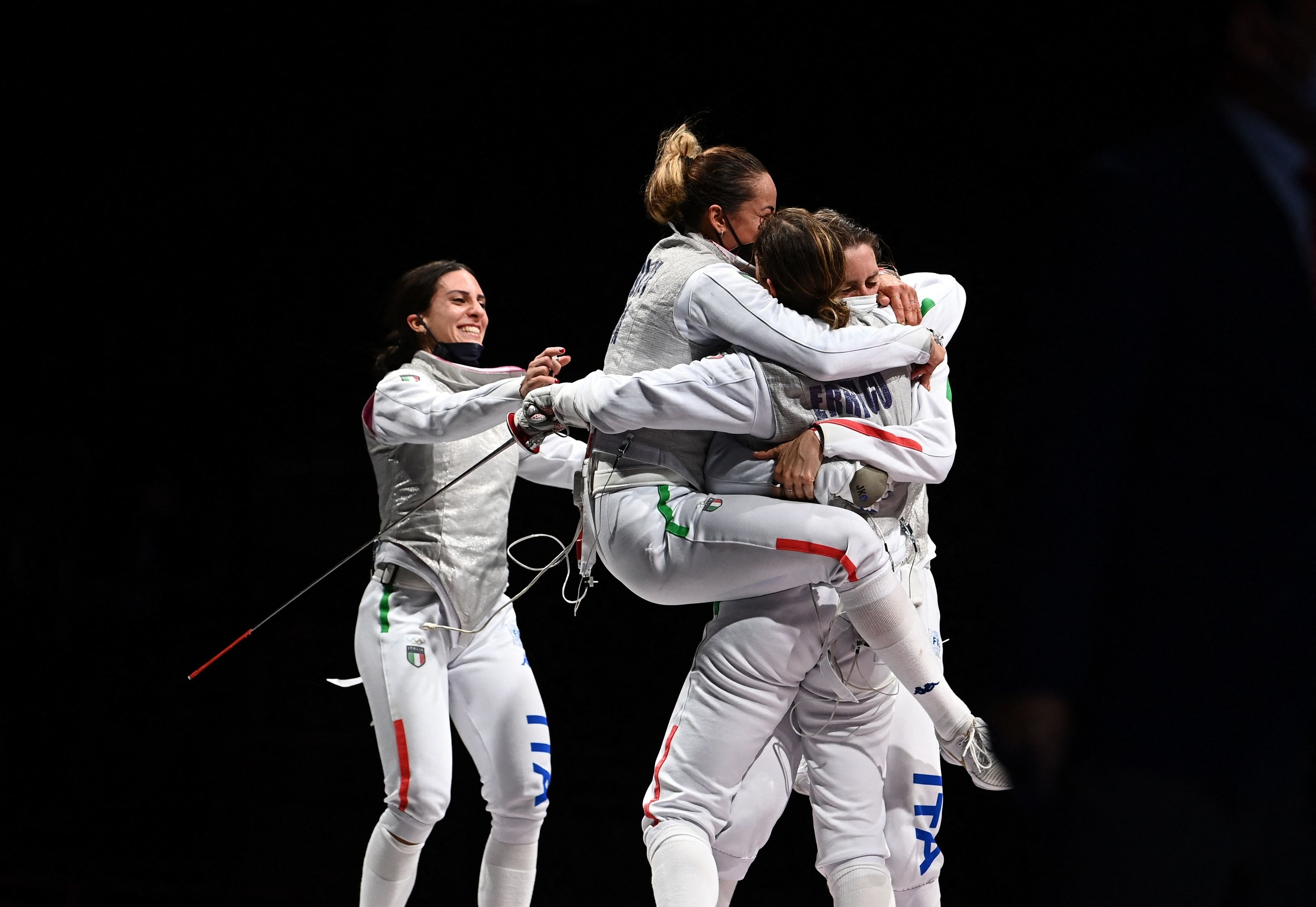 Four smiling women embrace in a group hug, one with her legs wrapped around another's chest in a close embrace