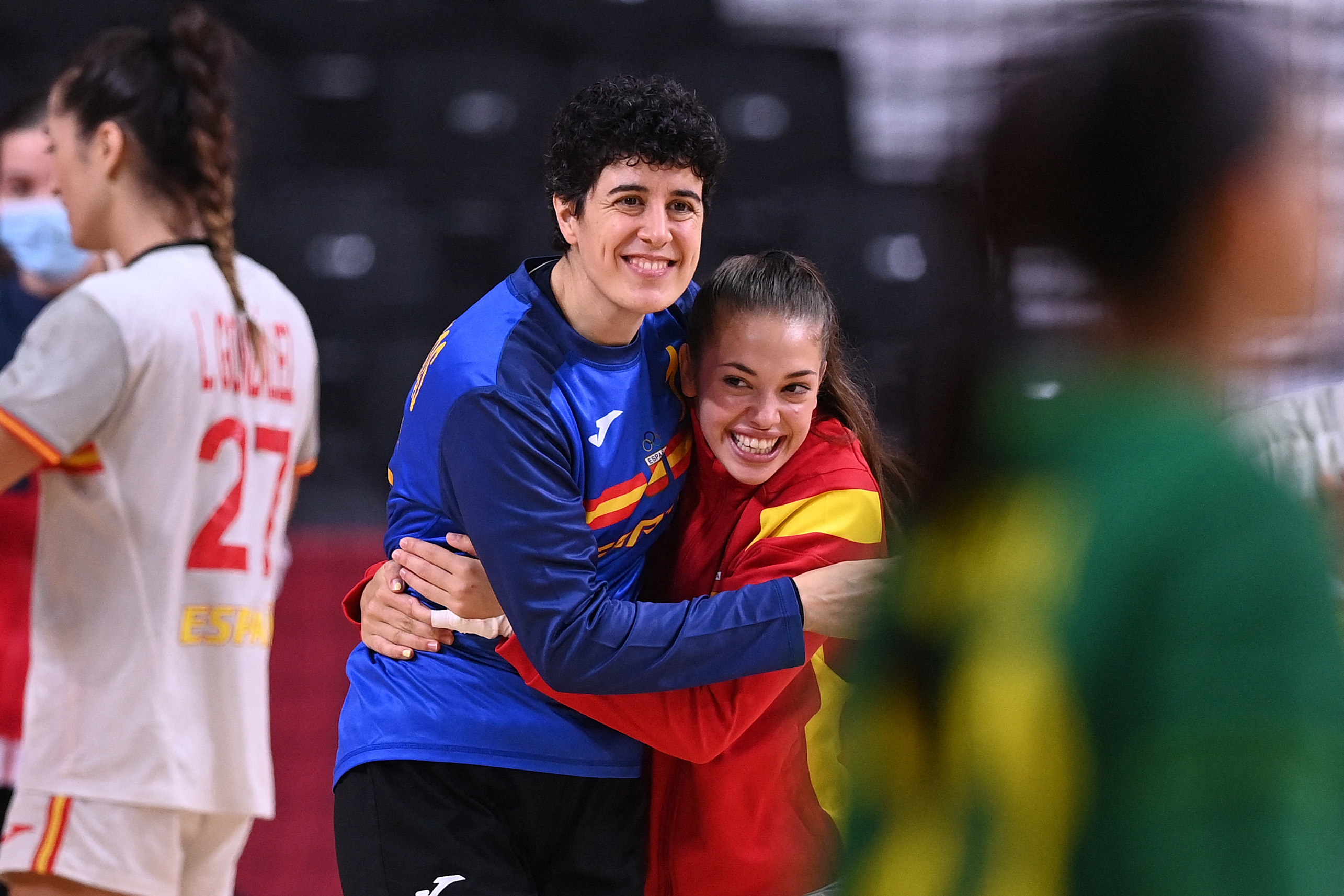 Spanish athletes hug and smile after competing in a handball match