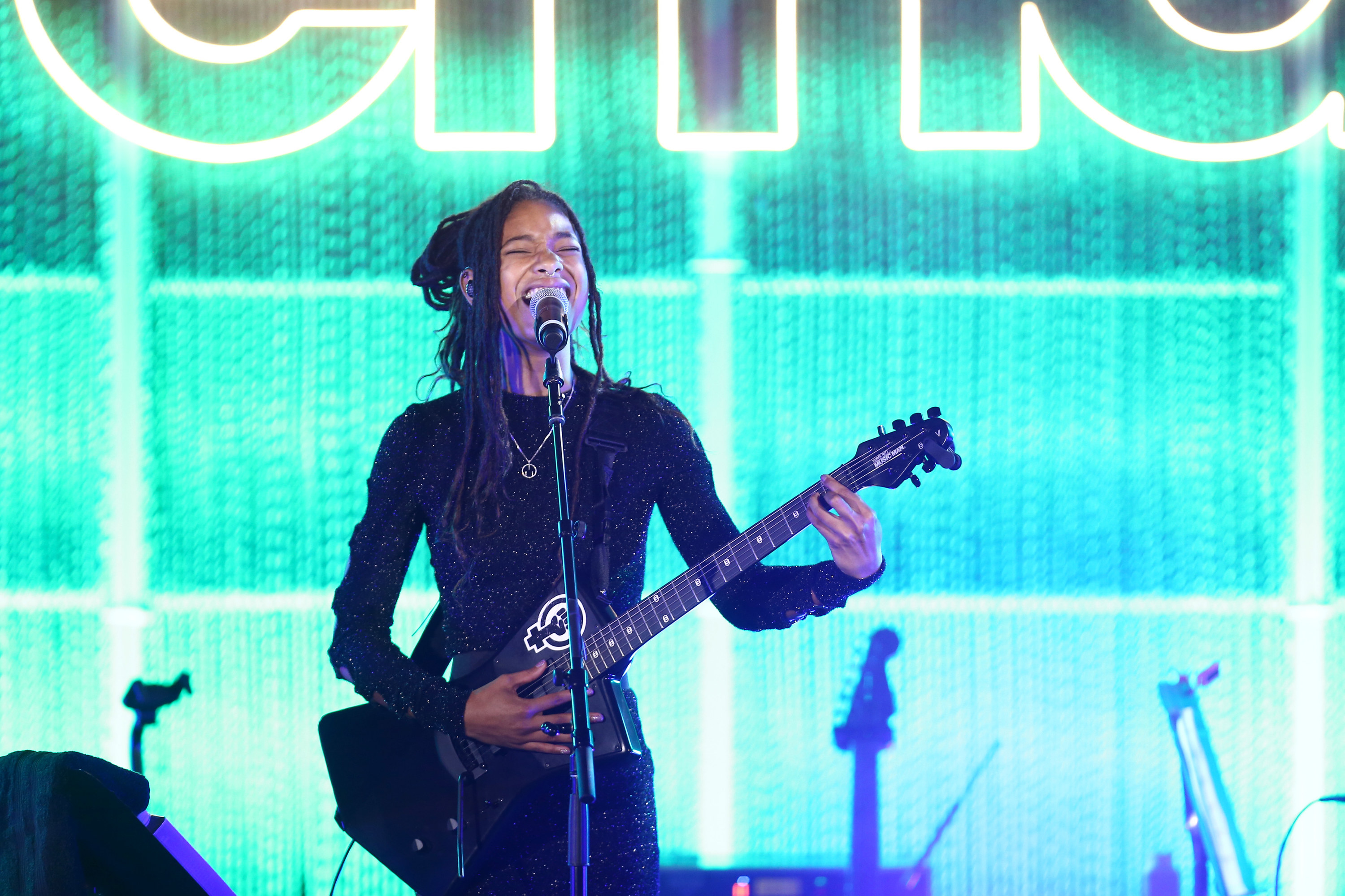 Willow Smith performs onstage with a guitar