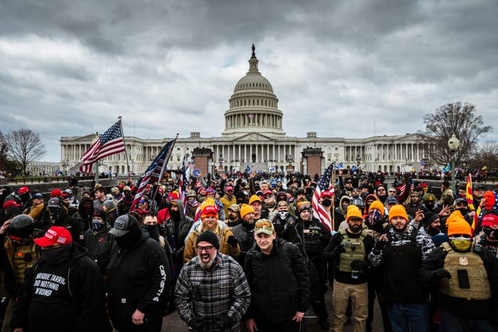 Hundreds of people, apparently mostly men, stand in front of the US Capitol with flags and some in tactical gear