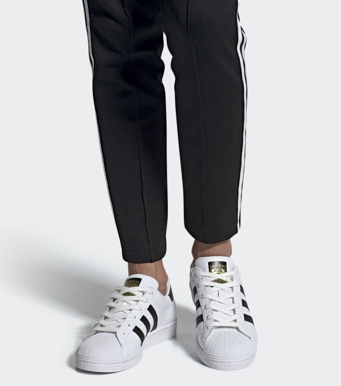 model wearing black and white superstar adidas shoes