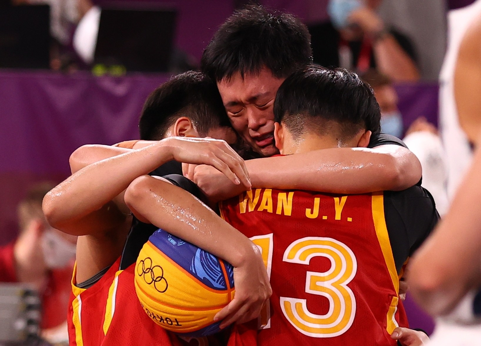 Chinese basketball players embrace and cry after competing in the Olympics