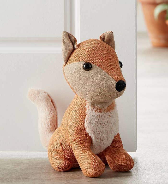 a fox shaped door stopper holding a door open