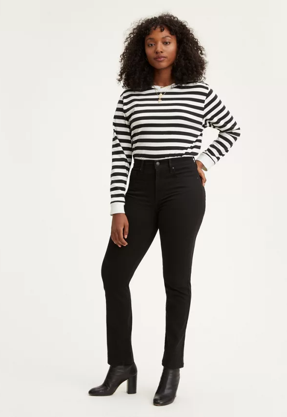 model wearing a pair of black straight jeans with a black and white striped shirt and black heeled booties