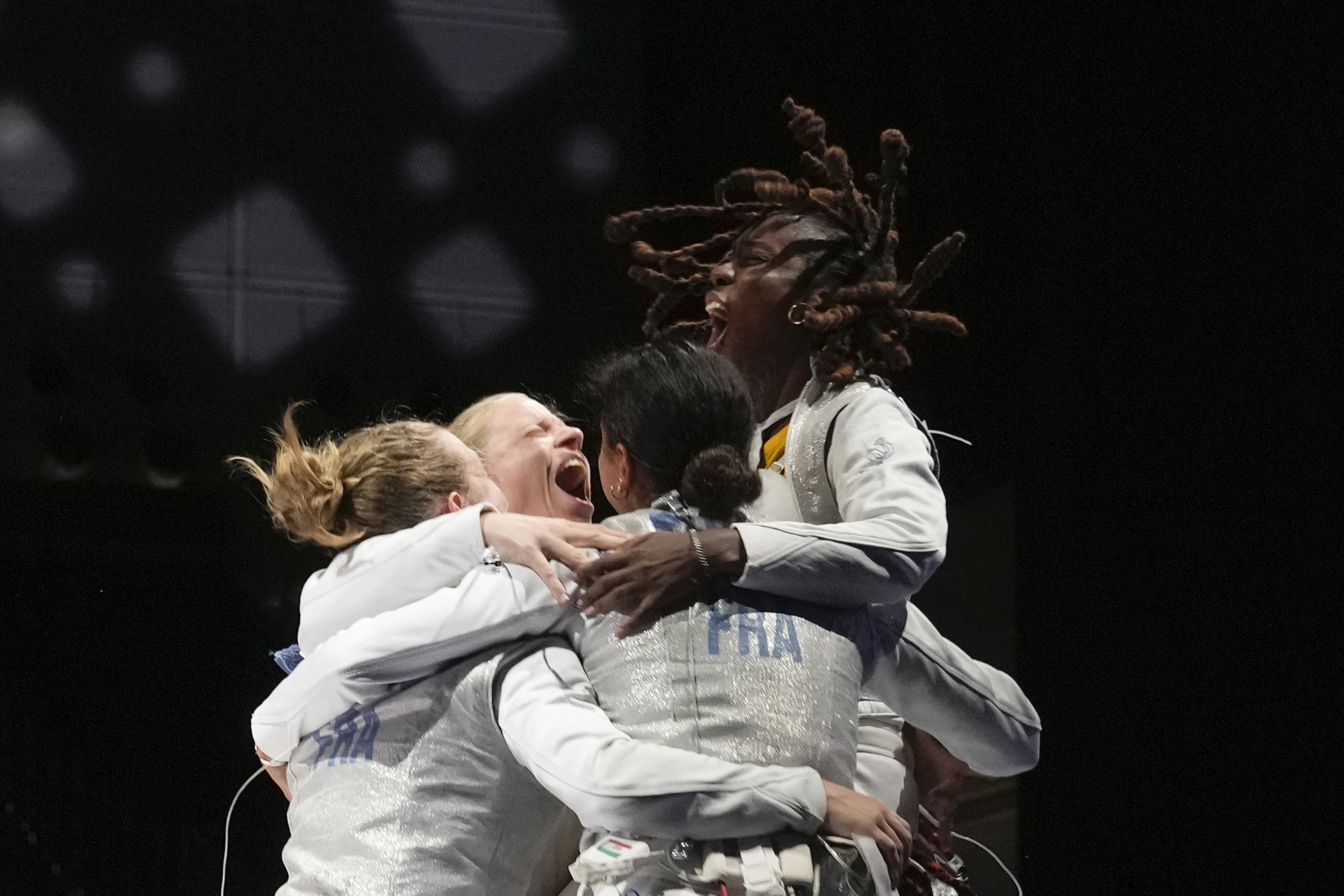 Female fencing athletes jump for joy after winning a match at the Olympics.