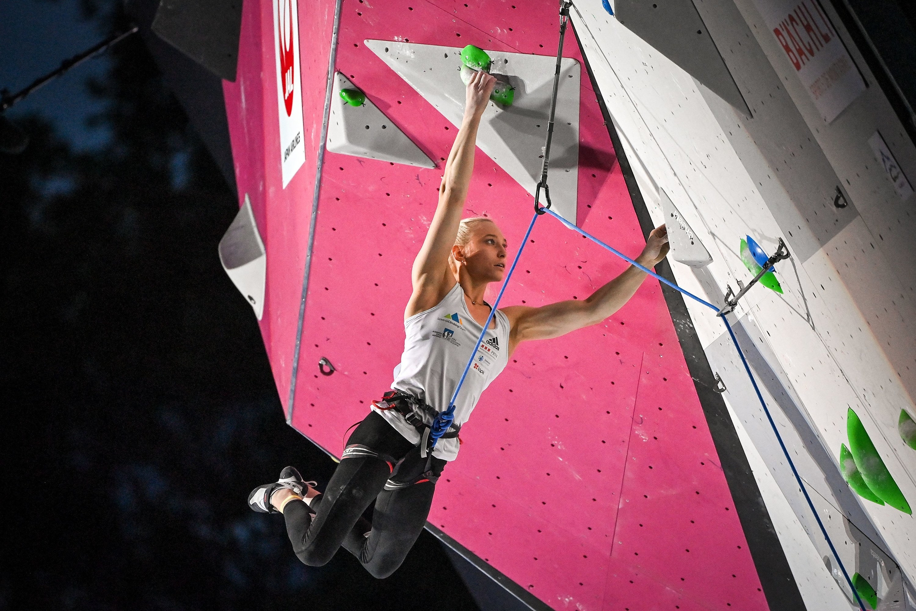 An Olympic rock climber hangs from a wall with a rope securing her