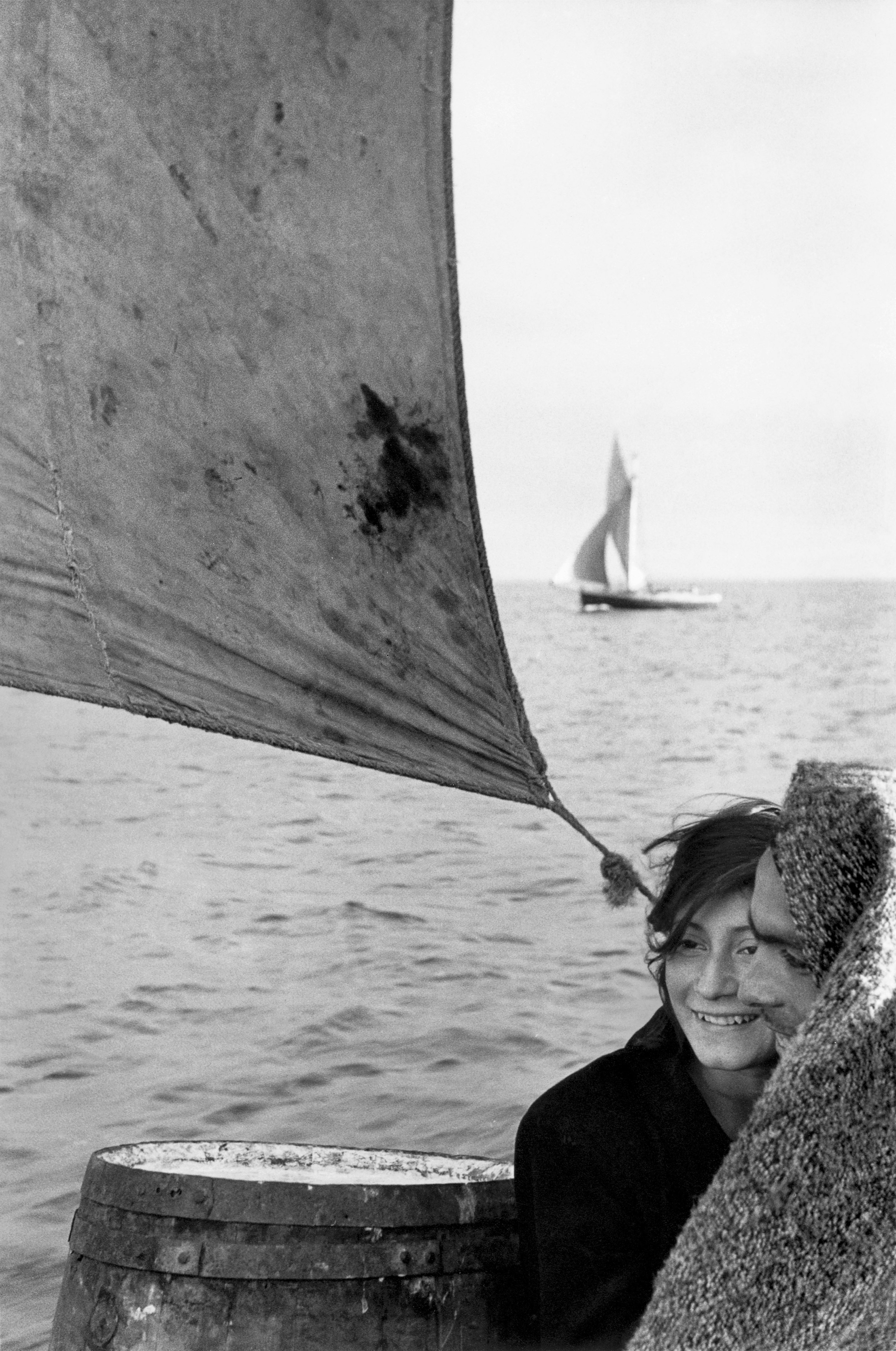 A young couple on a boat, with a sail above them and the woman smiling