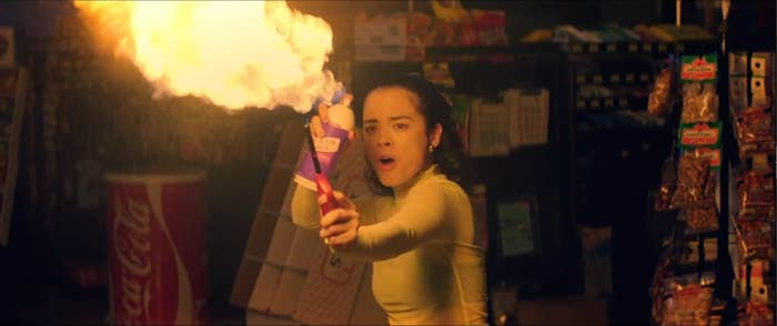 A girl flaring a flame by spraying alcohol on the flame.
