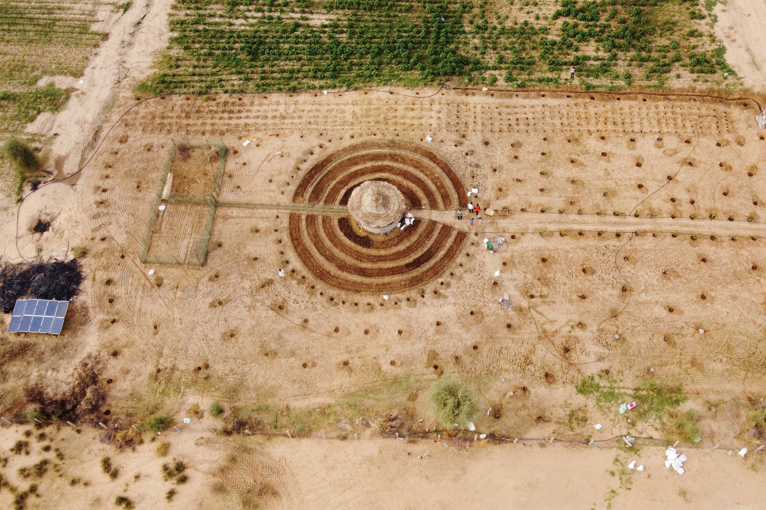 An overhead shot of a large series of circles carved into farmland, with people and solar panels nearby