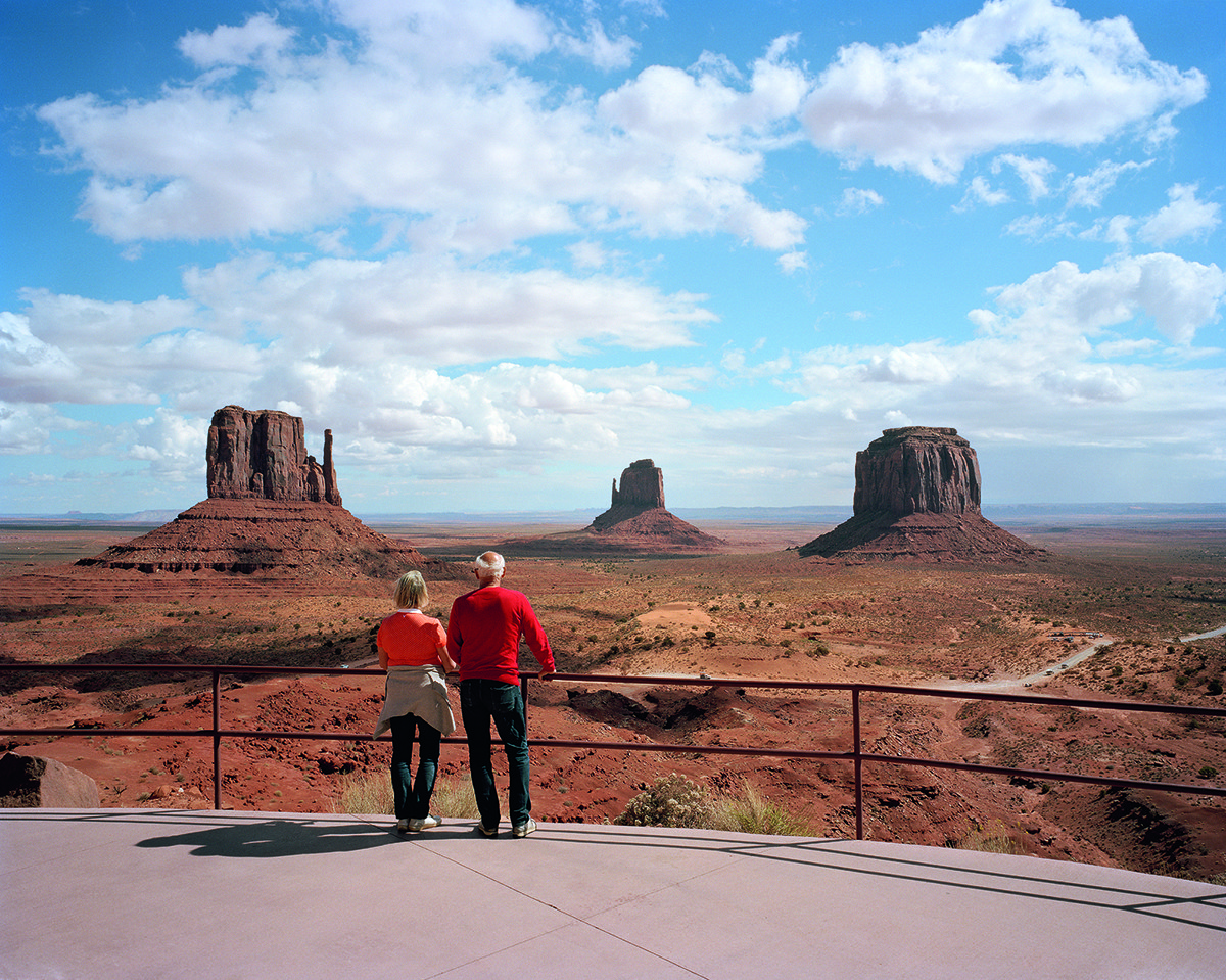 An older couple at a railing stare out at Butte Monuments in Monument Valley